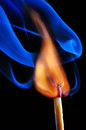 Burning match with blue smoke on black background Royalty Free Stock Photos