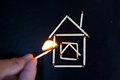 Burning match inear the model of the house in hand near Royalty Free Stock Photos