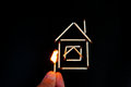 Burning match inear the model of the house in hand near Stock Photo
