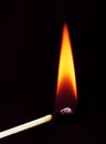 Burning matchstick on black background Stock Photography