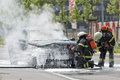 Burning motor vehicle been put out by firemen in protective clot Royalty Free Stock Photo
