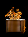 Burning toaster with two slices of toast caught on fire over black background Stock Images