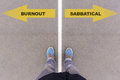 Burnout or sabbatical text on asphalt ground, feet and shoes on