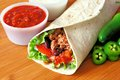 Burrito with salsa filled meat and vegetables and peppers on wood Stock Images