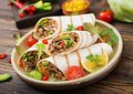 Burritos wraps with beef and vegetables on a wooden background. Beef burrito , mexican food. Royalty Free Stock Photo