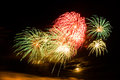 Bursts of green red and yellow fireworks colorful with the moon in the background Royalty Free Stock Photo