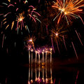 Bursts of pink fireworks reflected in a murky lake Royalty Free Stock Photos