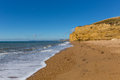 Burton Bradstock beach Dorset England UK Jurassic coast with sandstone cliffs and white waves in summer with blue sea and sky Royalty Free Stock Photo