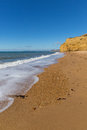 Burton Bradstock golden beach Dorset England UK Jurassic coast with sandstone cliffs and white waves in summer with blue sea Royalty Free Stock Photo