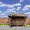 Bus shelter an old wooden with red brick wall and blue sky Royalty Free Stock Photos