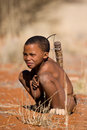 Bushman child san sitting in the desert in a early cold morning Stock Photos