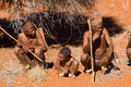 Bushman family of san tribe demostrating how to hunt in the desert Royalty Free Stock Images