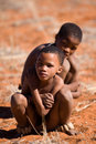 Bushman san boy boys while watching in a hunting day in namibia Stock Image