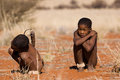 Bushman san boys while watching in a hunting day in namibia Royalty Free Stock Photos