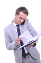 Busiensman checking his notes young attractive businessman in nice suit looking at schedule half body white background Stock Photos