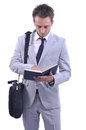 Busiensman take notes young attractive businessman in nice suit looking at his schedule half body white background Stock Photo