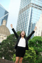 Business achievements success businesswoman in hong kong celebrating goals with arms raised up as winner young mixed race Royalty Free Stock Photo