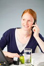 Business assistant or secretary on the phone a relaxed female behind her desk talking a mobile and looking away from camera Stock Images