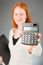 Business assistant showing a calculator smiling young female accountant or to the camera Royalty Free Stock Photos