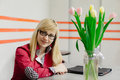 Business beautiful blonde girl with tulips sitting at the table Royalty Free Stock Photo
