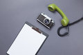 Business board and green handset with retro camera on grey background Royalty Free Stock Photos
