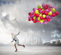 Business break young businesswoman running with bunch of colorful balloons Royalty Free Stock Photo