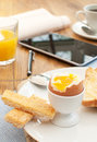 Business breakfast boiled egg and toast with a tablet and newspaper Royalty Free Stock Images
