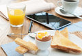Business breakfast table with and mobile tablet pen and newspaper Royalty Free Stock Image