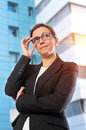 Business brunette woman with glasses posing in front of office building Royalty Free Stock Photography