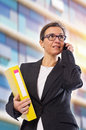 Business brunette woman with yellow folder and cellphone posing in front of office building Stock Photography