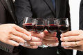 Business celebration with wine close up of human hands cheering up flutes of Royalty Free Stock Photo