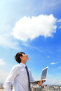 Business and cloud computing concept young man using laptop look to blue sky with cityscape in the background Royalty Free Stock Photos