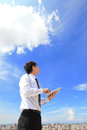 Business and cloud computing concept young man using tablet pc look to blue sky with cityscape in the background Stock Photography