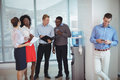 Business colleagues discussing by water cooler Royalty Free Stock Photo