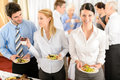 Business colleagues serve themselves at buffet Stock Photos
