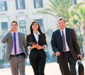 Business colleagues walking outdoors. Royalty Free Stock Image