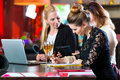 Business colleagues working with documents in a cafe young women or or restaurant they together and having fun they are good team Royalty Free Stock Images