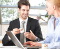 Business colleagues working on a laptop smiling in the office Royalty Free Stock Images