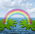 Business communication success concept with two islands shaped as a gear or cog wheel divided by ocean connected by a rainbow Stock Image