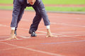 Business competition a businessman on a track ready to run Royalty Free Stock Image