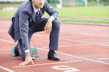Business competition a businessman on a track ready to run Royalty Free Stock Photos