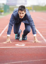 Business competition a businessman on a track ready to run Royalty Free Stock Images