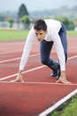 Business competition a businessman on a track ready to run Stock Photography