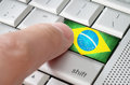 Business concept male finger pressing brazil enter key on metallic keyboard Royalty Free Stock Photo