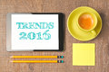Business concept of trends for 2016 new year. Digital tablet with coffee cup on wooden desk. View from above. Royalty Free Stock Photo