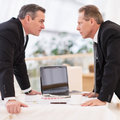 Business confrontation two mature men in formalwear conflicting while standing face to face Stock Photo