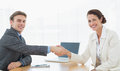 Business couple shaking hands in office Stock Photo