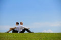 Business couple sitting back to back on grass Royalty Free Stock Photo