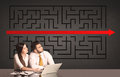 Business couple with a solved puzzle in background Royalty Free Stock Photo