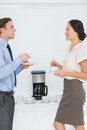 Business couple with tea cups chatting in office Royalty Free Stock Photo